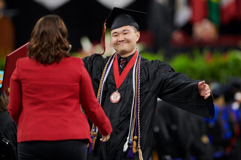 Bascom student getting a hug from friend after graduation