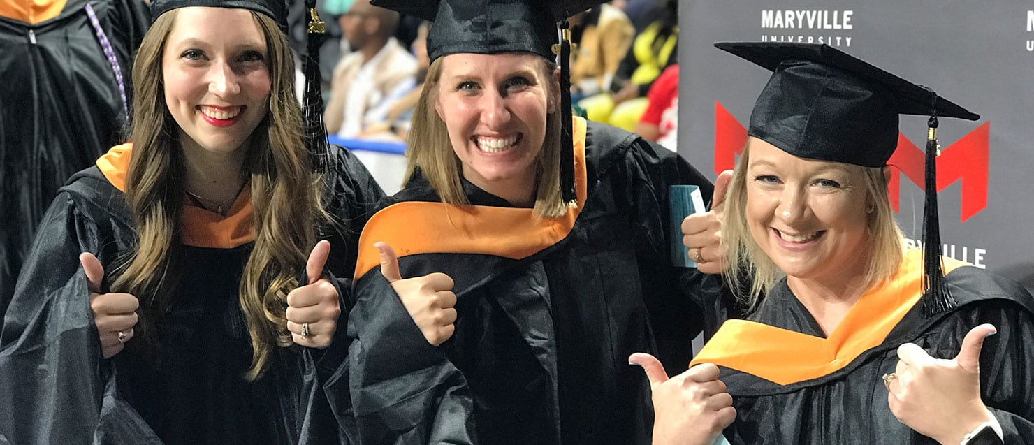 three students who give a thumbs up sign during graduation ceremony