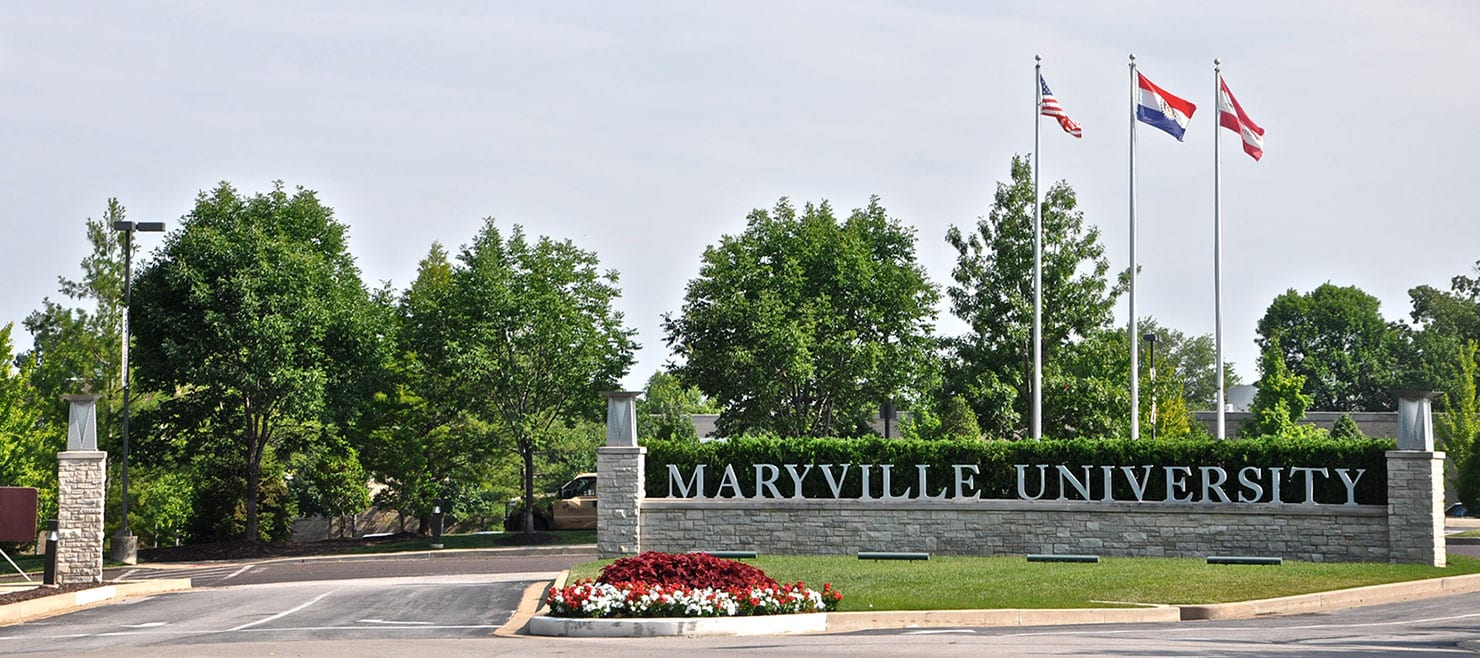 Entrance to Maryville University with flags and sign
