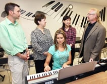 Louis Michael, music department coordinator at Lewis and Clark, gives a tour of a music lab to Cynthia Briggs, director of Maryville's music therapy program, and Soo-Jin Kwoun, associate professor of music therapy.