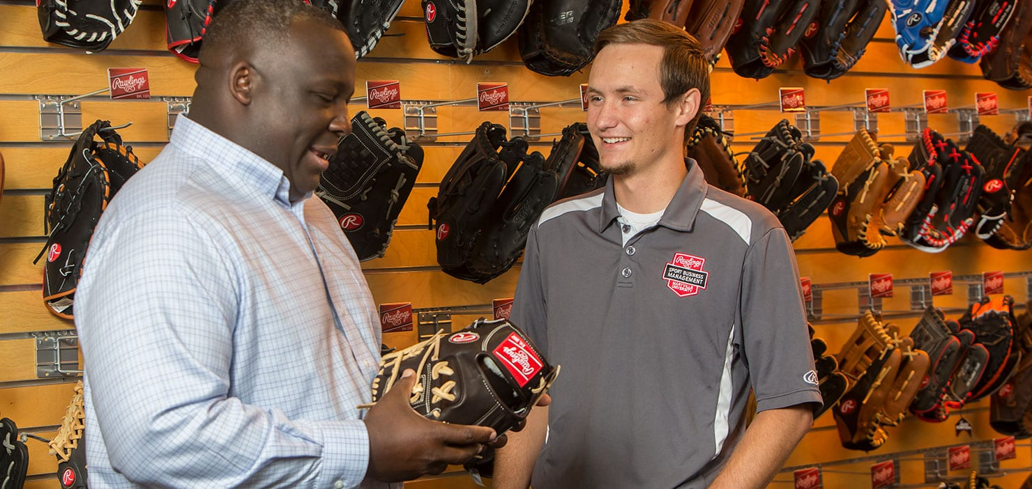 student in rawlings showroom with jason williams, director of rawlings sport business management program