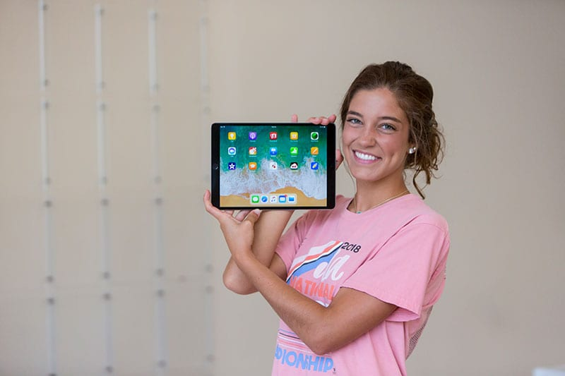student holding up an iPad