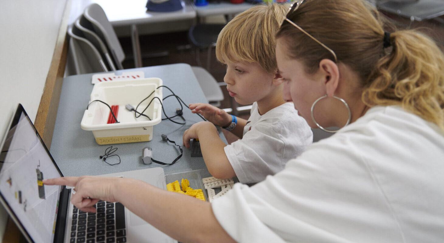 teacher helping student learn about robotics