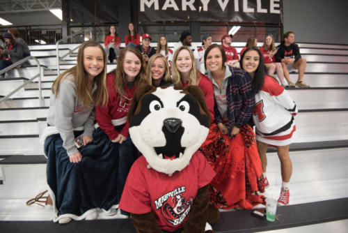 Louie with students watching ice hockey game